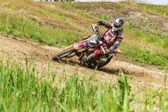 motocross O motociclista em uma curvatura apressa-se ao longo de uma estrada de terra, sujeira voa de debaixo das rodas Close-up imagens de stock