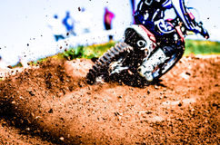 Motocross Biker Accelerating in a Curve With Flying Mud and Debris. Debris floating all around during a motorcycle acceleration in a race Royalty Free Stock Photography
