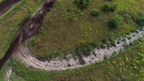 Motocross race driver speeding country terrain. Motocross race. Drivers speeding on cross country terrain. Aerial view stock footage