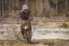 Motocross Race. Motocross driver on wet and muddy terrain in Finland stock images