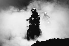 Motocross racer accelerating in dust track. Black and white, high contrast photo Stock Photos