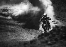 Motocross racer accelerating in dust track, Black and white photo. Motocross racer accelerating in dust track, Black and white, high contrast photo Royalty Free Stock Photo