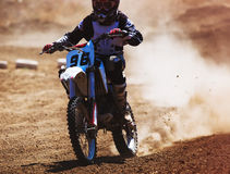 Motocross racer accelerating in dust track. Tinted photo Royalty Free Stock Image