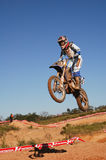Motocross racer comes off a jump during race Royalty Free Stock Image