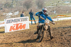 Motocross racer on corner. Motoccross racer with mud on motorbike in front of KTM Dementor billboard Royalty Free Stock Photo