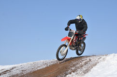 Motocross racer flying down the mountain Royalty Free Stock Image