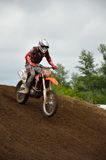 A motocross racer lands on the rear wheel Stock Photos
