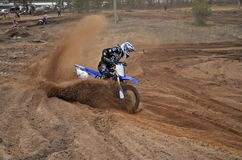 Motocross racer leaves the deep sandy ruts Stock Image