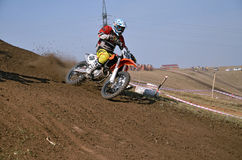 Motocross racer on a motorcycle the turns on a mountain slope Stock Photos