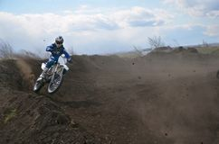 Motocross racer moves along sandy parapet turning track Royalty Free Stock Photos