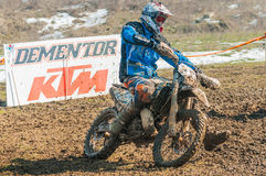 Motocross racer. With mud on motorbike in front of Dementor KTM billboard Stock Image