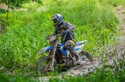 Motocross racer on mud Stock Photos