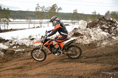Motocross racer rides in descent on the rear wheel Royalty Free Stock Photography