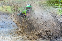 Motocross racer rides through the mud with big splash, royalty free stock photos