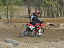Motocross Racer Riding on a Dirt Track Stock Image