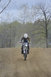 Motocross Racer Riding Down a Dirt Hill Stock Image