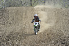 Motocross Racer Riding Down a Dirt Hill Royalty Free Stock Photos