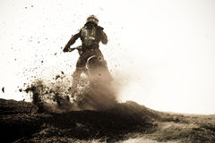 Motocross racer roosts dirt berm on track. Royalty Free Stock Photography