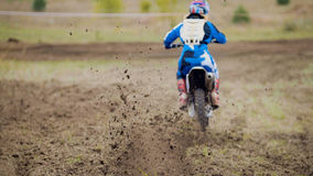 Motocross racer start riding his dirt Cross MX bike. Telephoto stock images