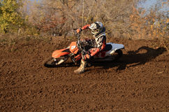 Motocross racer turns with large slope Royalty Free Stock Photos