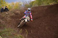 Motocross racer turns with large slope Royalty Free Stock Photography