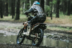 Motocross racer in a wet and muddy terrain Royalty Free Stock Photography
