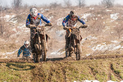 Motocross racers. With mud on motorbike climbing hill royalty free stock photos