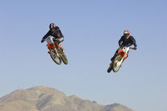 Motocross Racers Performing Stunt In Midair Against Blue Sky. Two male motocross racers performing stunt in midair against clear blue sky royalty free stock images