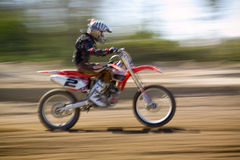 Motocross Racing. A motocross rider speeding around a dirt track royalty free stock images
