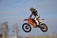 Motocross-Rennläufer führt einen effizienten Sprung durch Lizenzfreie Stockfotos