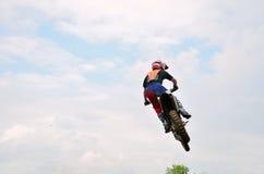 Motocross-Rennläufer fliegt unter den Wolken Stockbild