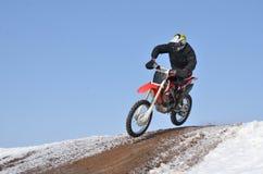Motocross-Rennläuferflugwesen hinunter den Berg Lizenzfreies Stockbild