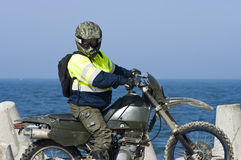 Motocross rider. A motocross rider wearing his protective sportswear - helmet, goggles. Sea (ocean) in the background stock photos