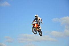 Motocross rider in the air, one-hand operation. Motocross rider high in the air on a motorcycle one-hand control, against the blue sky and clouds Stock Photography