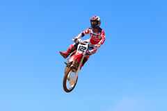 Motocross rider and bike clearing a tabletop jump. During the final heat of the race Stock Images