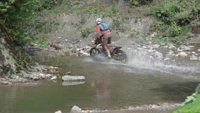 Motocross Rider Crosses il fiume Movimento lento stock footage