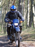 Motocross rider in dirt path. A motocross rider racing through a forest Royalty Free Stock Photography