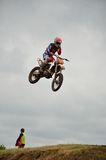 Motocross rider in flight removes protective film Royalty Free Stock Photography