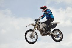 Motocross rider jump blue sky. Motocross rider performs jump located high in the air against the blue sky Royalty Free Stock Image