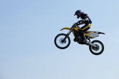 Motocross rider jumping. Motocross rider jumps into the sky Royalty Free Stock Image