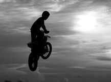 Motocross rider jumping happily. While floating in the sky like Stock Images