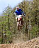 Motocross rider jumping a rise. Image shows a motocross rider speeding over a dirt track Royalty Free Stock Photos