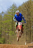 Motocross rider jumping a rise. Image shows a motocross rider speeding over a dirt track Royalty Free Stock Images