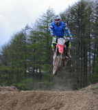 Motocross rider jumping a rise Royalty Free Stock Photo