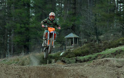 Motocross rider jumping a rise Stock Photos