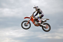 Motocross rider jumps high against the sky. Motocross rider on the motorbike performs efficient flight is hanging in the open air royalty free stock photography