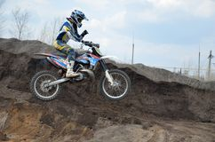 Motocross rider jumps over an earthen pit. Motocross rider on a motorbike jumps over an earthen pit driving with one hand Royalty Free Stock Photos
