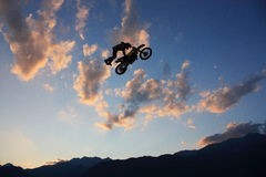 Motocross rider in midair. Side view of silhouetted motocross rider jumping high in air with blue sky and cloudscape background, Daboot Freestyle Motocross show Royalty Free Stock Images