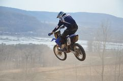 Motocross rider on the motorbike performs flight. Motocross rider on the motorbike performs efficient flight is hanging in the open air Stock Images