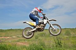 Motocross rider on a motorcycle in the air. Against the sky and mountains Stock Image